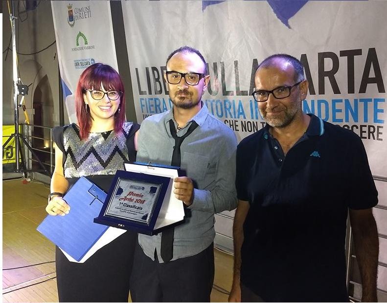 Andrea Spinilli, al centro, con Daniela Melone che ha presentato la cerimonia di premiazione e Luigi Lorusso, editore e giurato, che ha consegnato il premio.